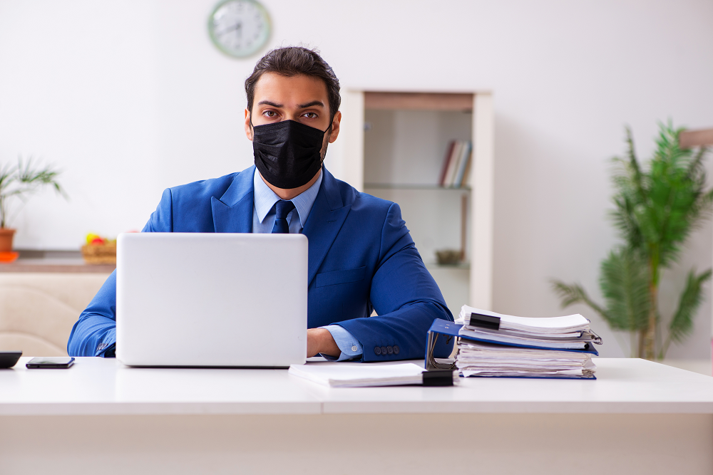 Man in mask at computer